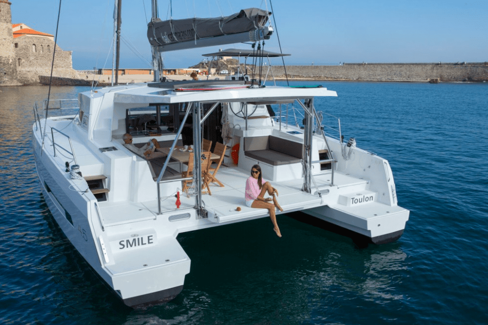 Rear of an anchored Bali 4.5 with a woman in pink shirt on the transom