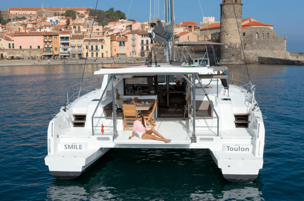 Rear of an anchored Bali 4.5 with a woman in pink shirt on the transom with a beautiful old town in the background