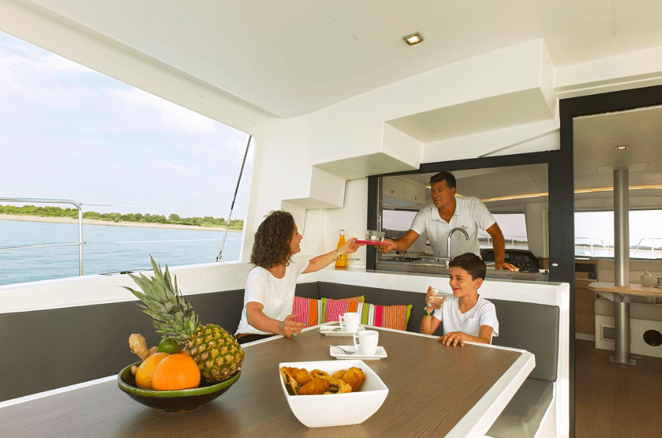 Man, woman and child having a great sunny day on deck of the Bali 4.5, eating a meal