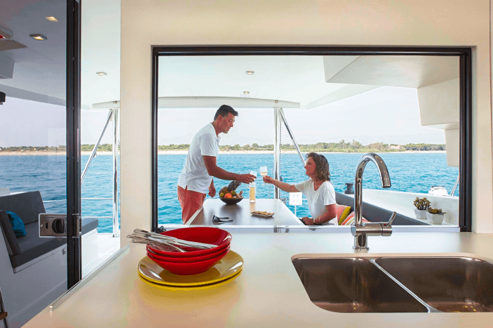 Man and woman having a glass of wine in the cockpit of the Bali 4.5 yacht with the sink of the galley in the foreground