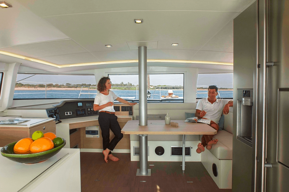 Saloon of the yacht Bali 4.5 with a man and a woman in it talking. Fruit bowl in the foreground