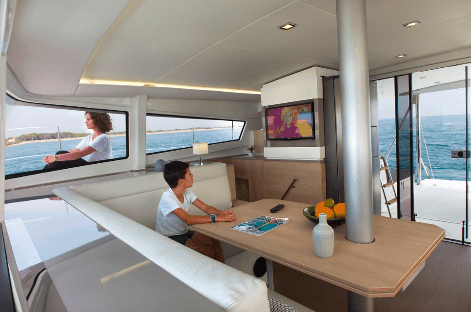 The saloon of the Bali 4.5 with a boy in it watching cartoon while a woman chills outside the window on deck