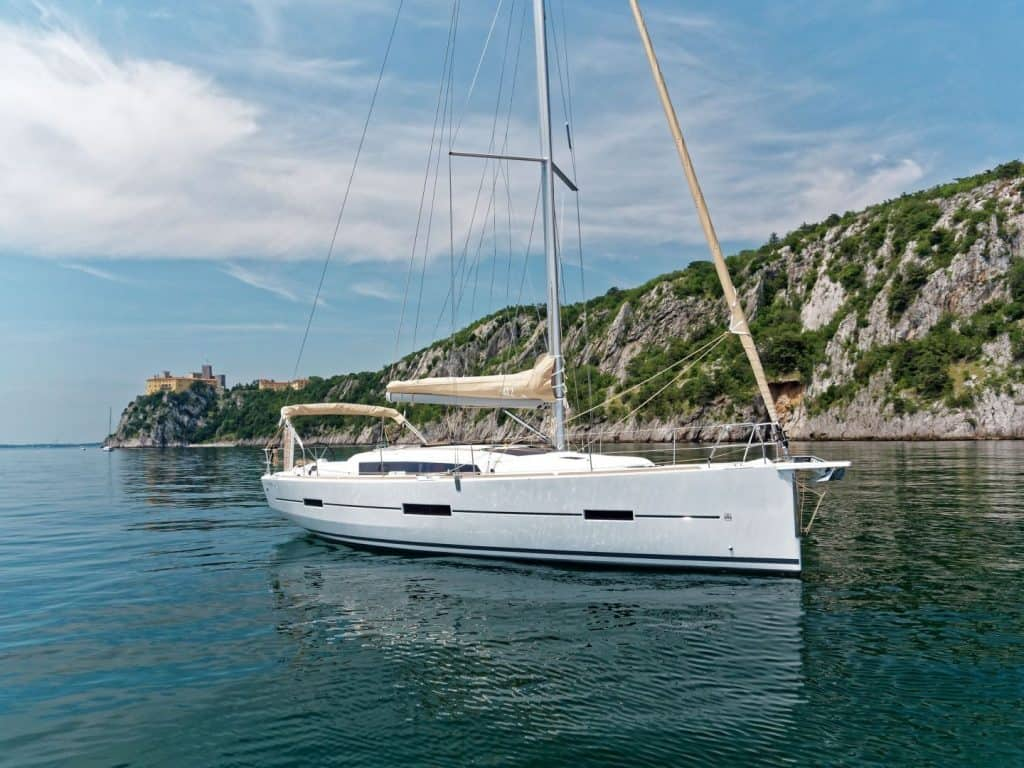 Dufour grand large 412 floating on still water close to a rocky coastline