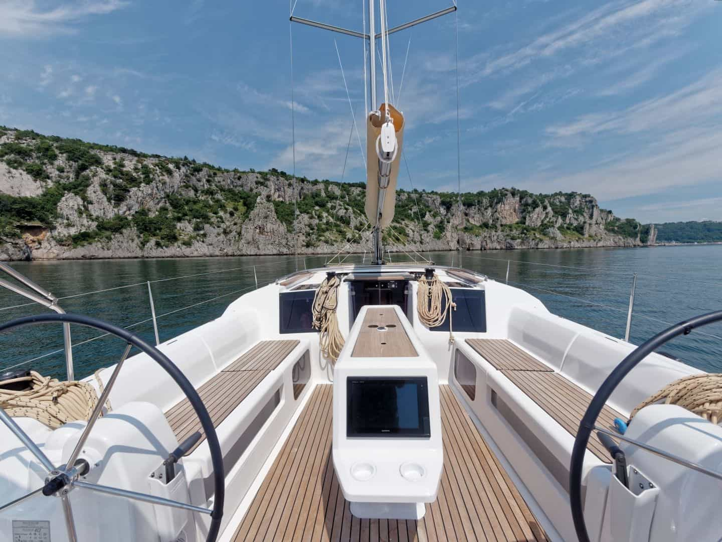 Deck of the Dufour grand large 412. The yacht is approaching beautiful cliffs on a sunny still day