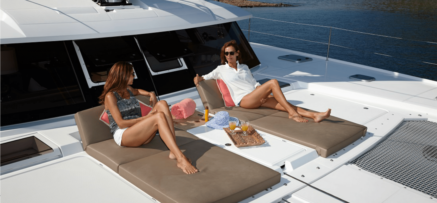 Mother and daughter enjoying the sun on the spacious front deck of the Pajot Ipanema 58