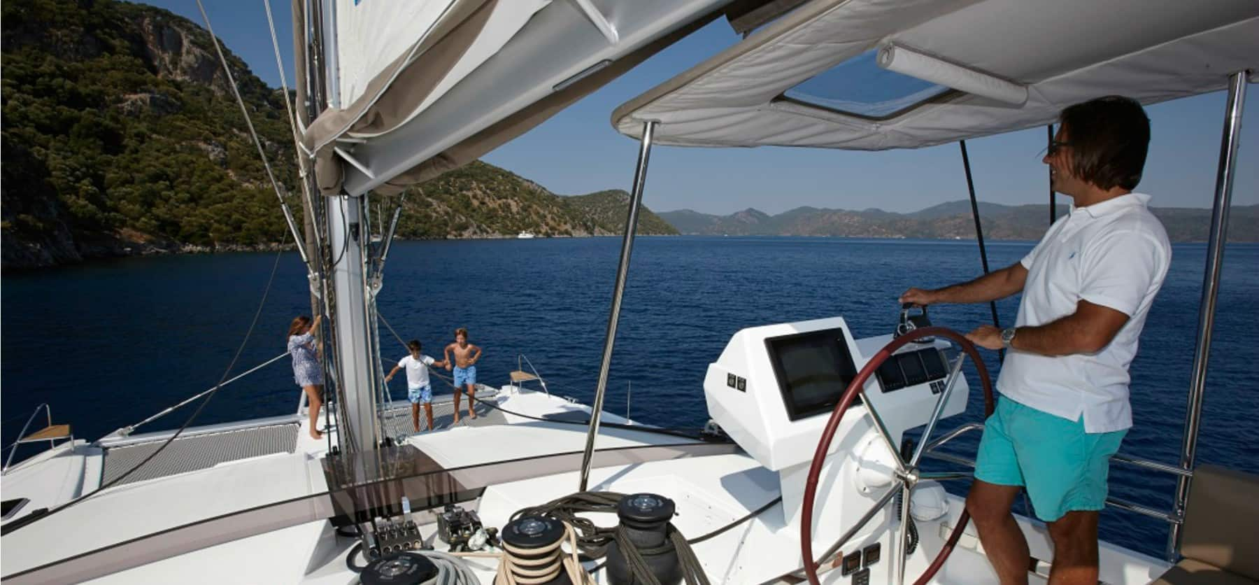 Father navigating the boat while watching his family enjoying the massive front deck of the Pajot Ipanema 58
