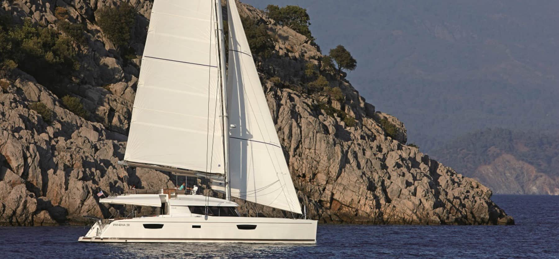 The Pajot Ipanema 58 in action, sliding through the calm waves along side beautiful coastline