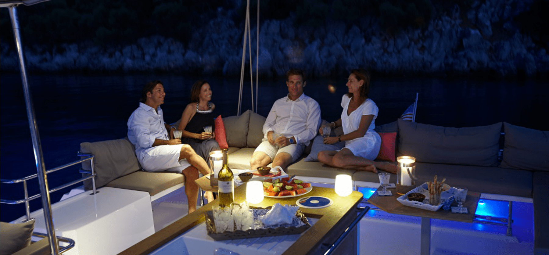 2 couples enjoying a beautiful and romantic evening on the cockpit area of the Pajot Ipanema 58