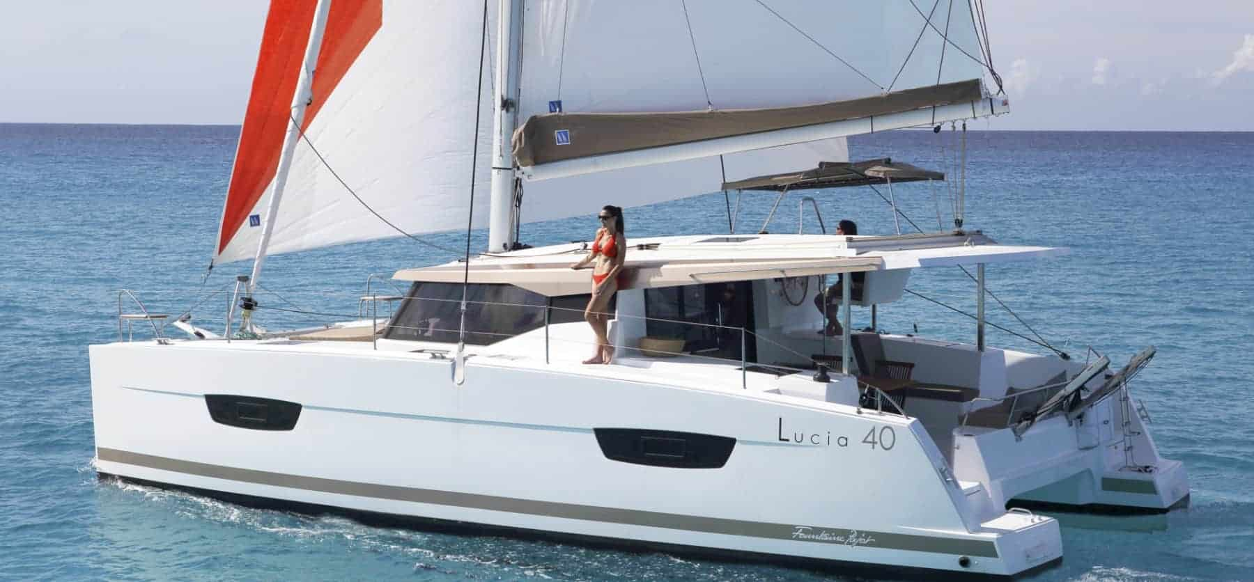 The very stylish Fountaine Pajot Lucia 40 sailing ahead while a woman in red bikini stands on deck looking out over the ocean