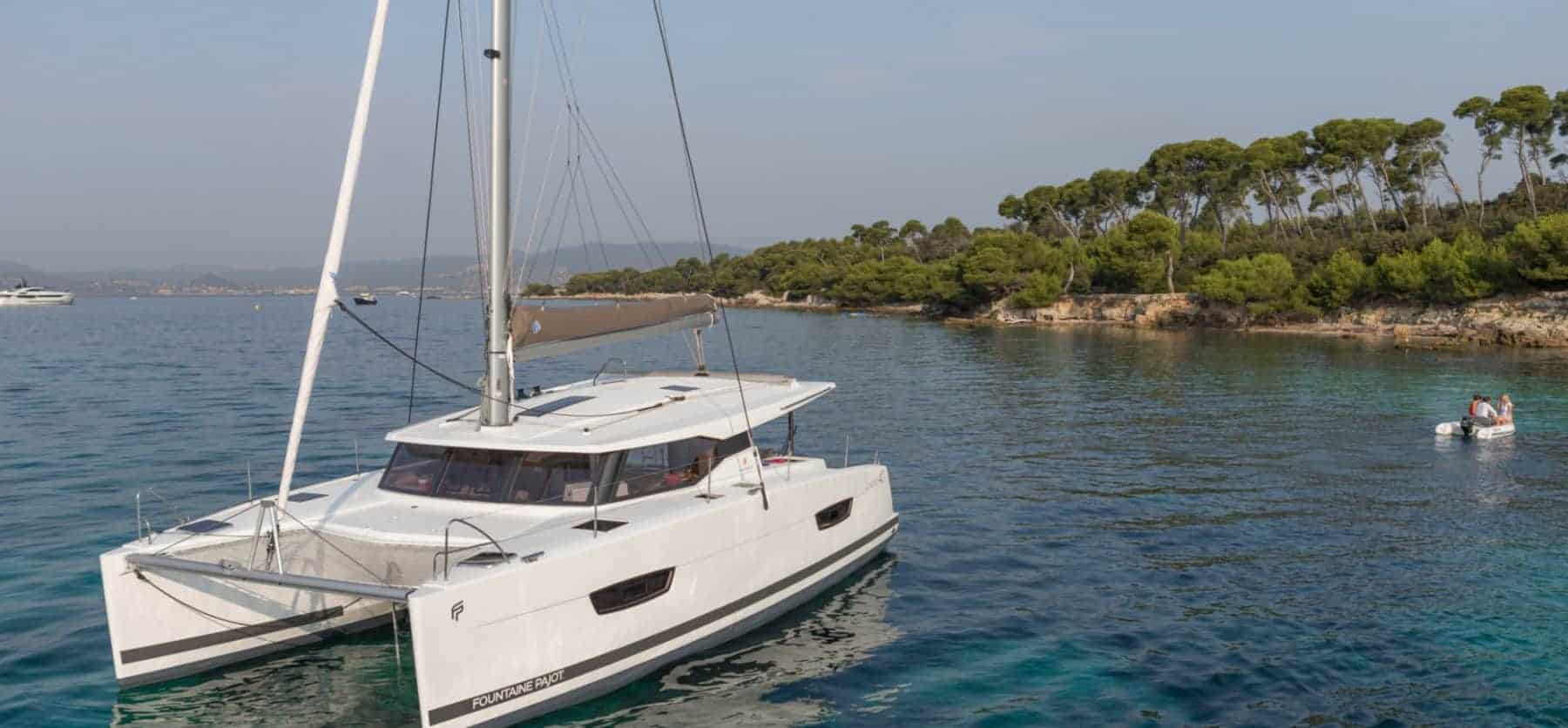 Fountaine Pajot Lucia 40 anchored close to a tropical landscape and a small boat with people in it going to the shoreline