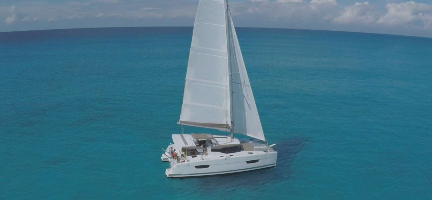 Fountaine Pajot Lucia 40 floating ahead with its sail up looking elegant in the crystal clear water