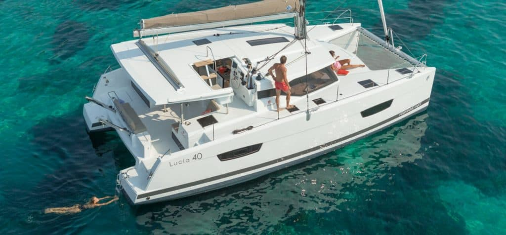 A woman sunbathing on the front deck of the Fountaine Pajot Lucia 40 while another woman is swimming behind the yacht in nice blue water