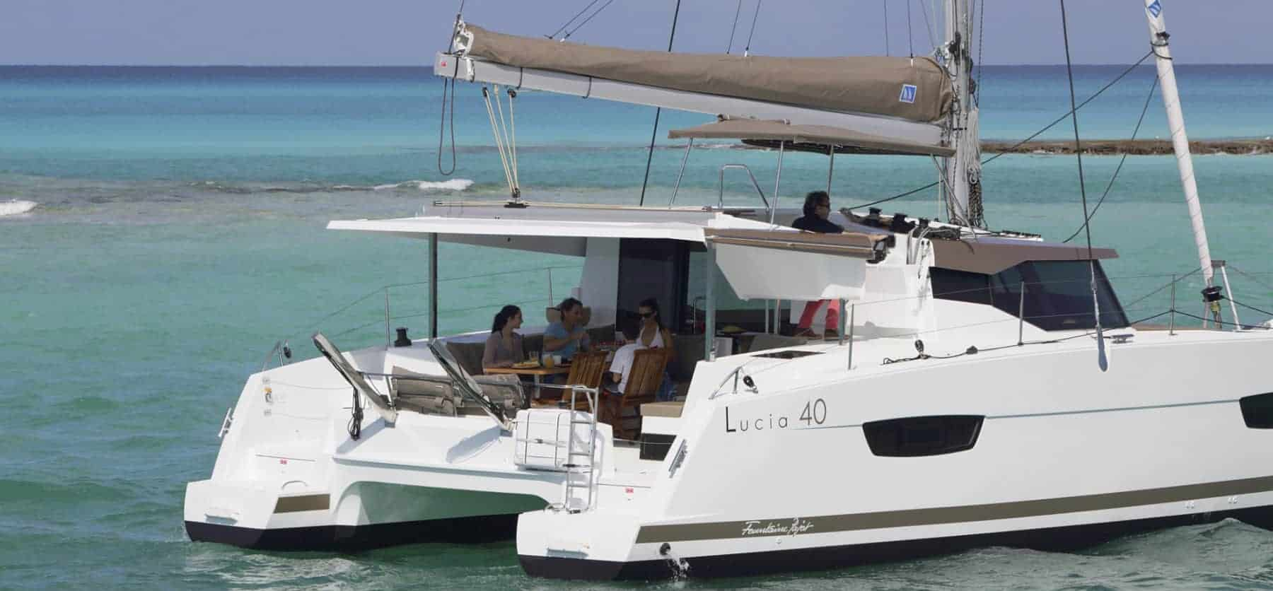 People having dinner on deck of the Fountaine Pajot Lucia 40 while a man sits on the flybridge a sunny day
