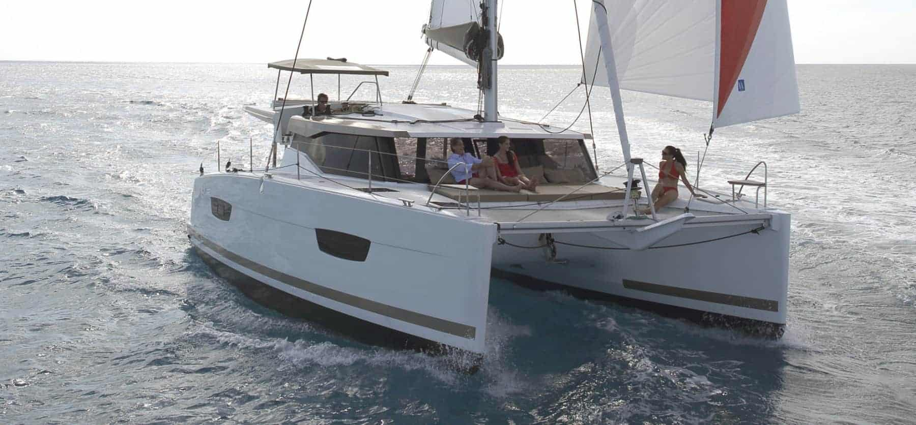 Fountaine Pajot Lucia 40 with wind in its sail a cloudy day and people chilling on the front deck