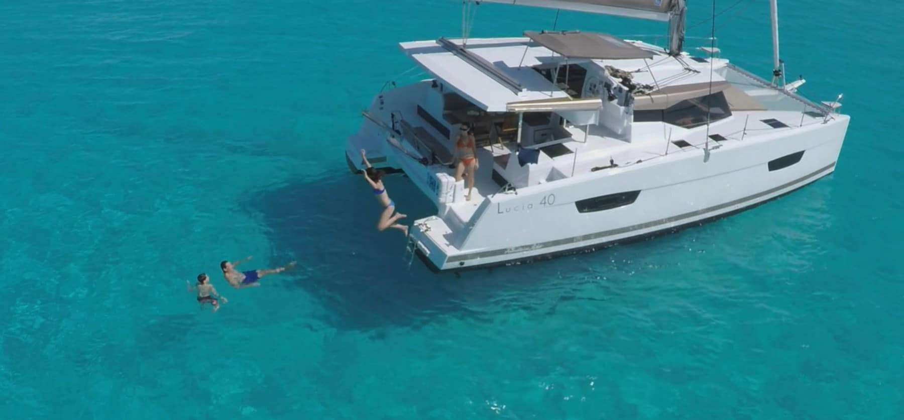Two couples having a great time bathing in the crystal clear water that the Fountaine Pajot Lucia 40 is floating in