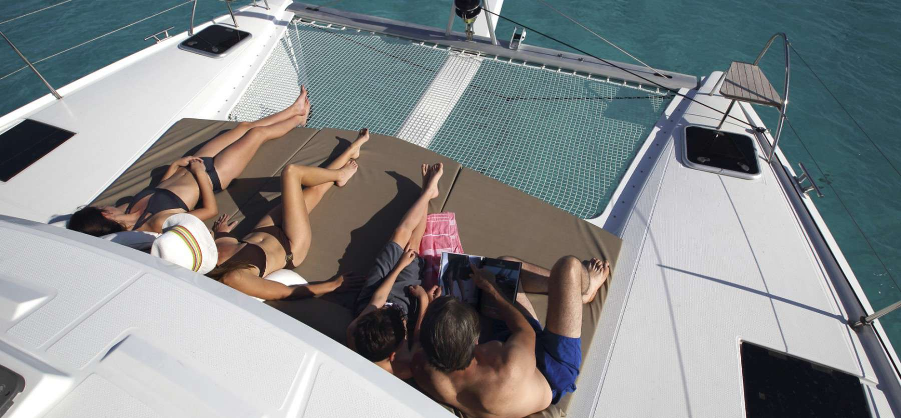 two women and two men sunbathing on the front deck of the stylish Fountaine Pajot Lucia 40
