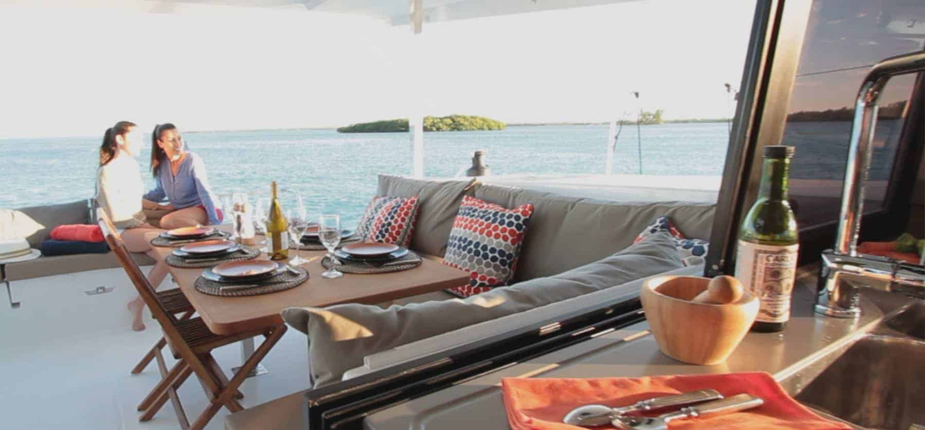 Two girls having a conversation on deck on a Fountaine Pajot Lucia 40 a sunny day and with a set dinner table
