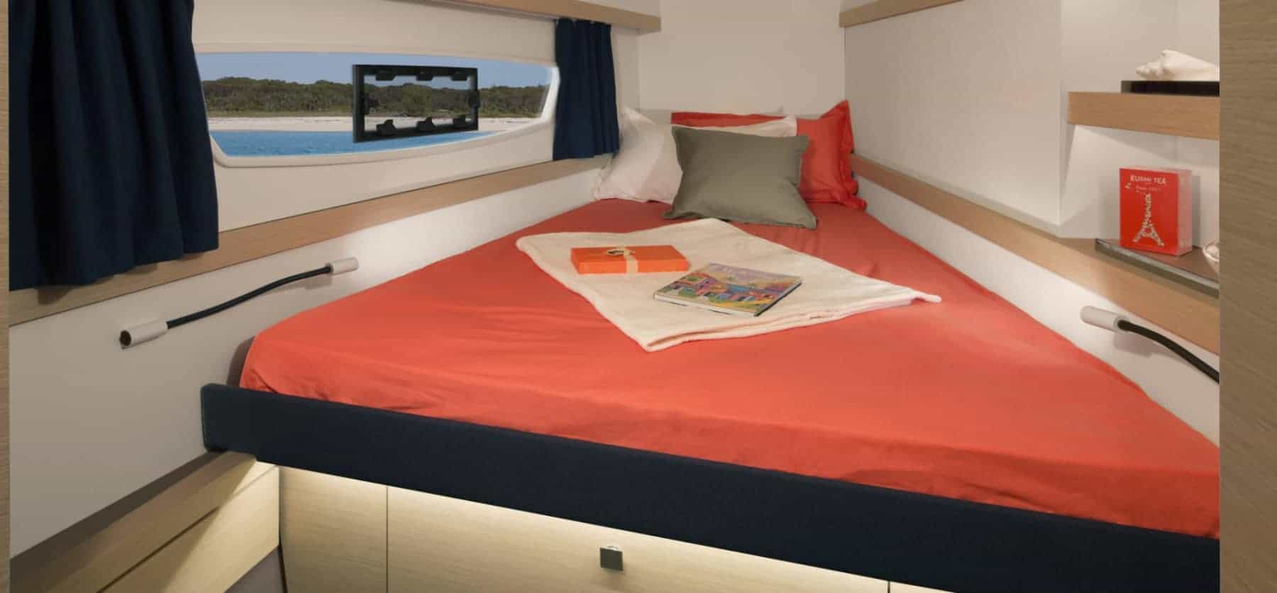 Inside of a cabin in the Fountaine Pajot Lucia 40 with red bed sheets and with walls and a window beside the bed