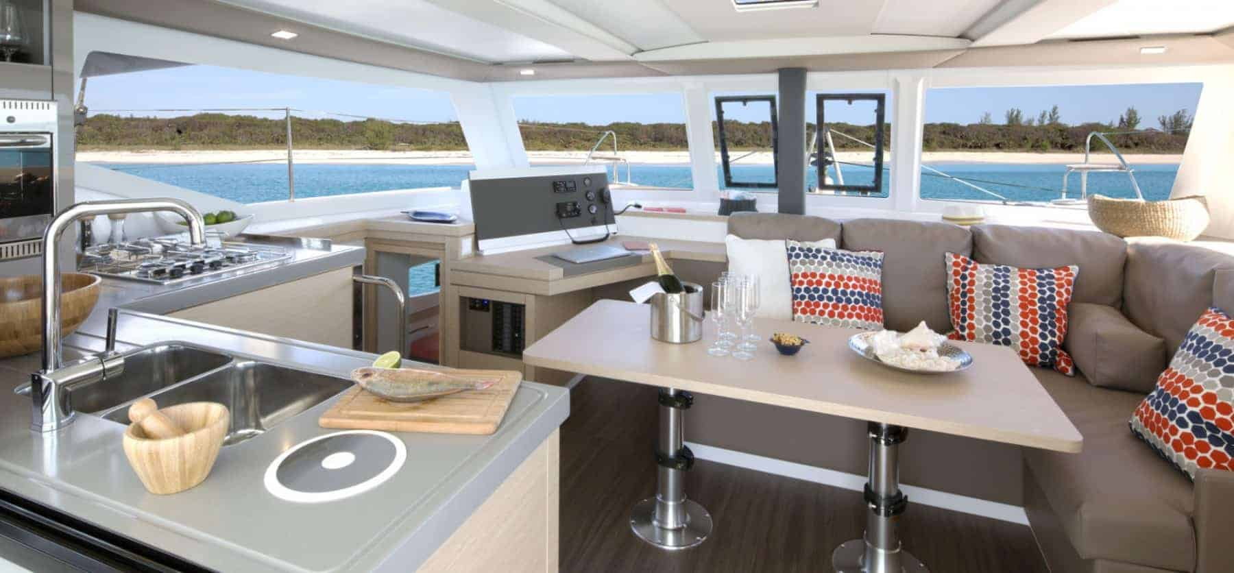 The beautiful, home feeling galley of the Fountaine Pajot Lucia 40 with a nice beach in the background