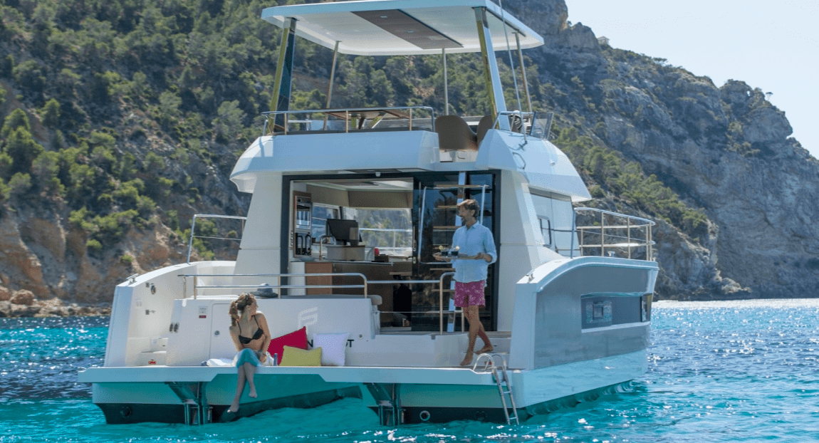 Couple getting ready for some drinks and an romantic evening on the trasom of the Fountaine Pajot Motor Yacht 37