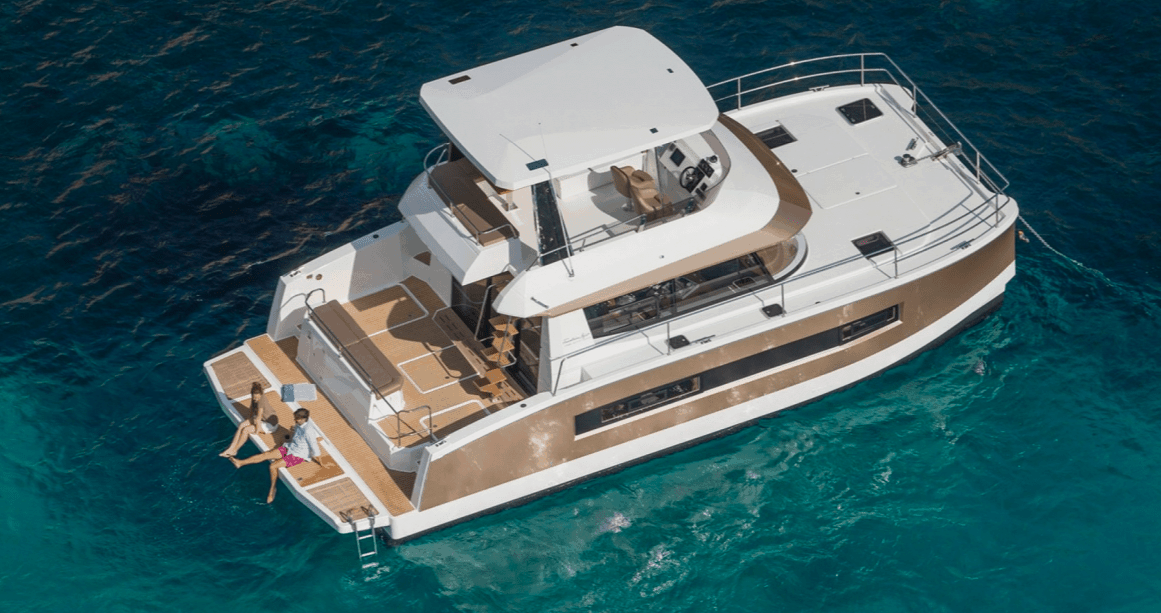 Couple relaxing on the transom of thir anchored Fountaine Pajot Motor Yacht 37
