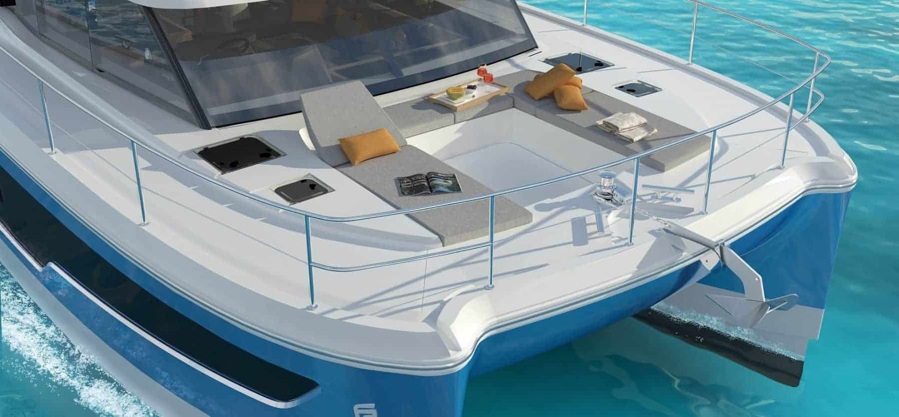 The stylish front deck of a Fountaine Pajot Motor Yacht 40 with magazines and a tray of fruits on the loungers