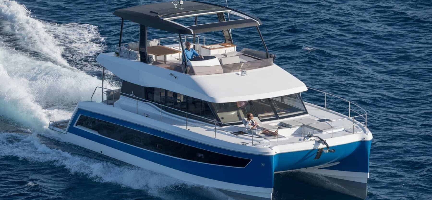 Aerial view of the Fountaine Pajot MY 44 in action with the motors running and a man at the steering wheel and a woman chilling on front deck