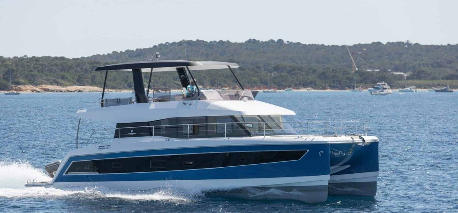 The beautiful Fountaine Pajot Motor Yacht 44 cruising away from the tropical landscape that is seen in the background
