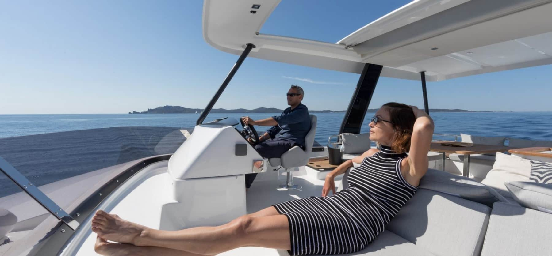 A man at the steering wheel on the flybridge of Fountaine Pajot MY 44 while a woman sits next to him relaxing and enjoys the breeze of the ocean