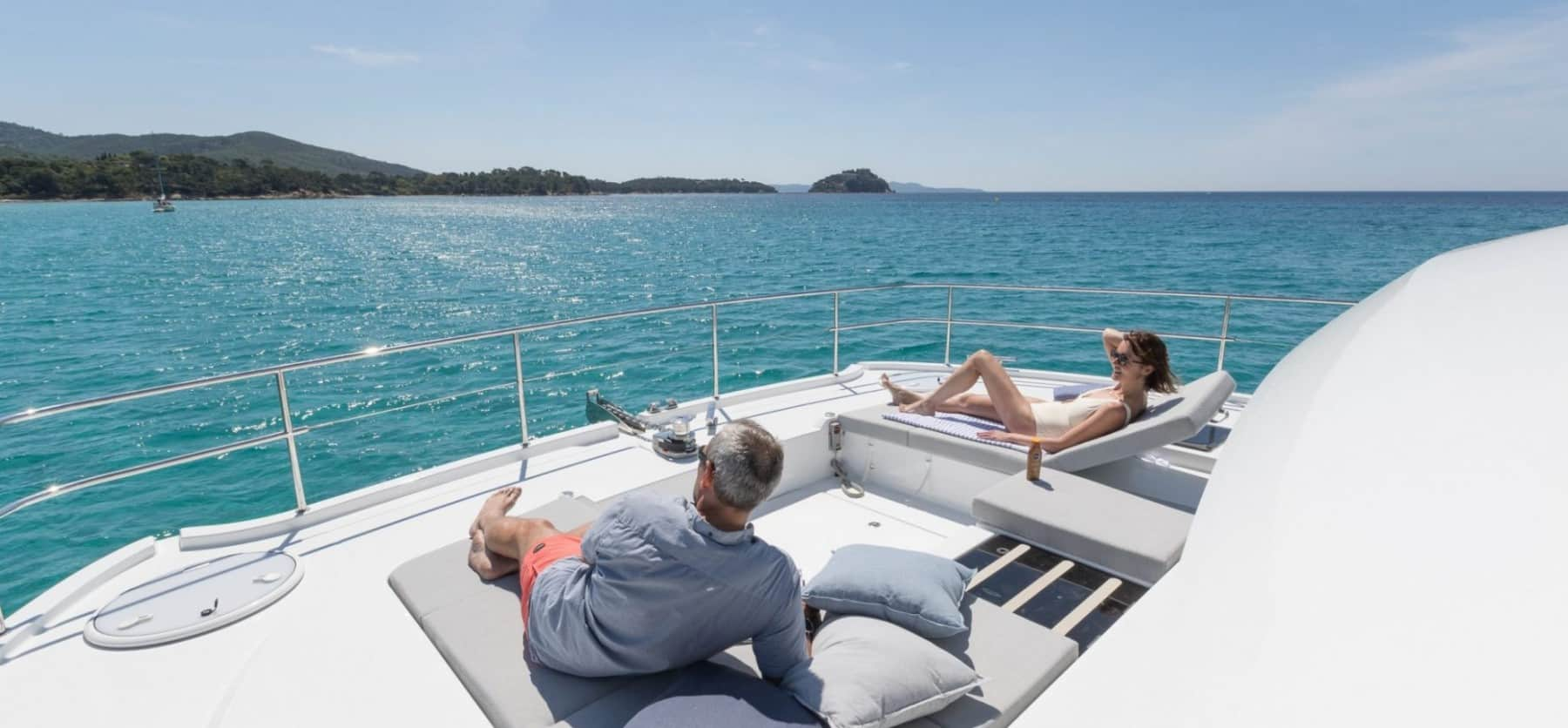 A man and a woman sunbathing on deck of a Fountaine Pajot MY 44 while looking out over the beautiful blue waters