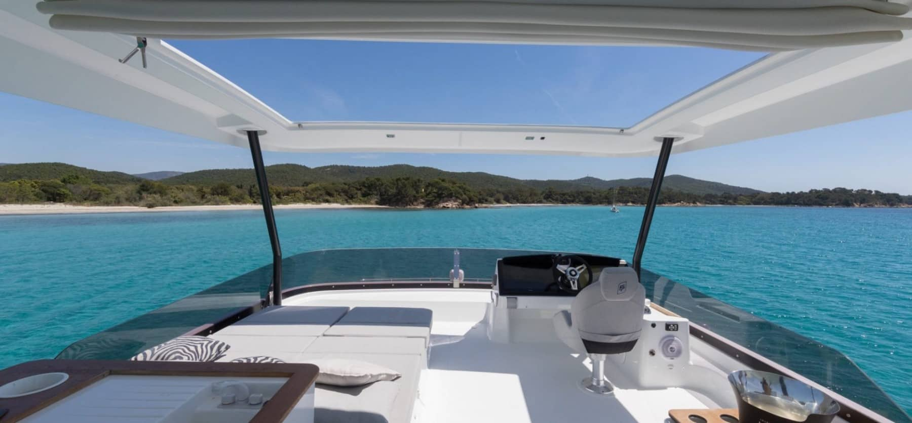 View from the gorgeous flybridge of a Fountaine Pajot MY 44 thats floating in clear, blue water and has a tropical island ahead of it