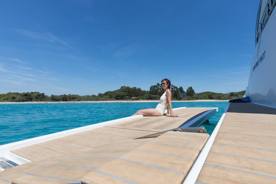A woman in a swimsuit on the deck of the Fountaine Pajot Motor Yacht 44 sunbathing and dipping her feet in the tropical, blue water