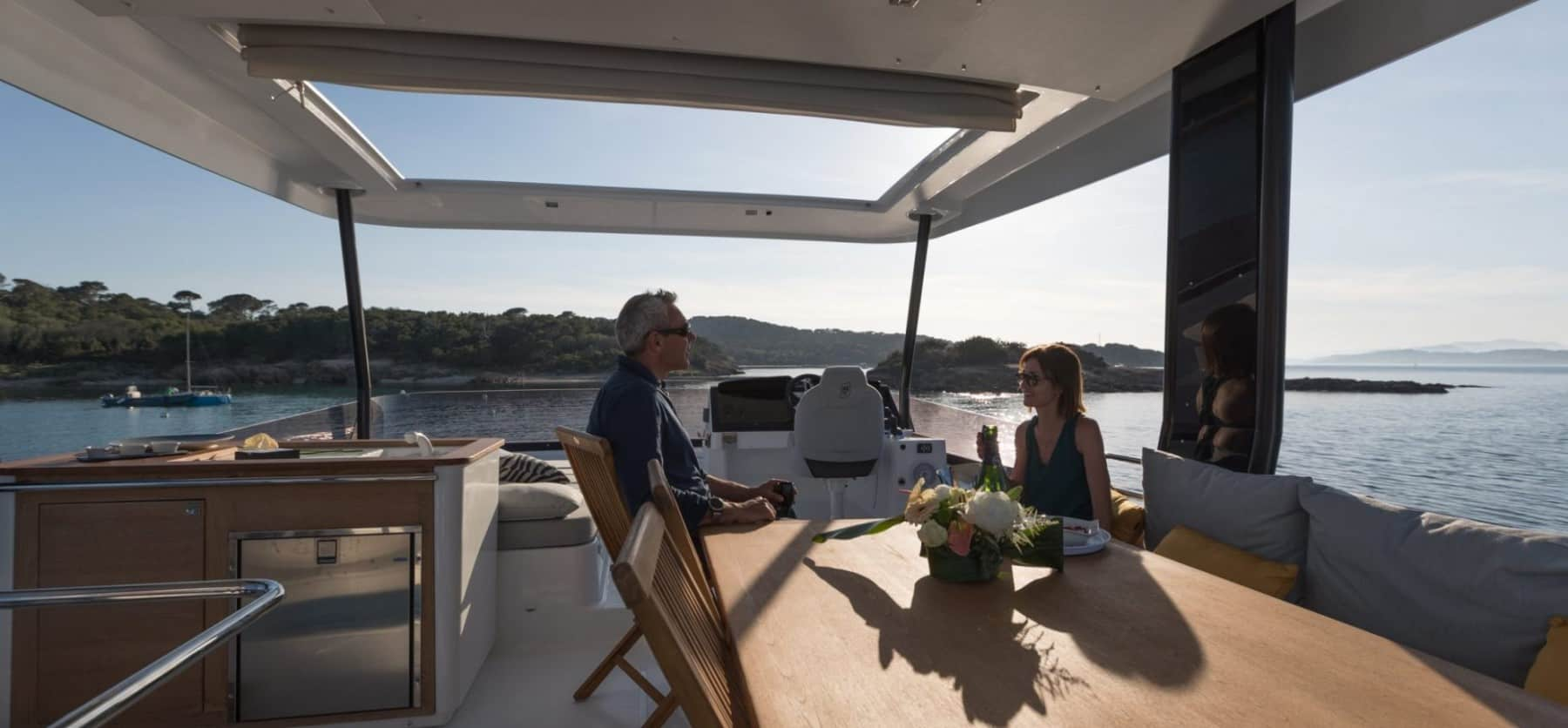 A man and a woman having a conversation on the flybridge of the Fountaine Pajot Motor Yacht 44 with tropical shores and the sun in the background
