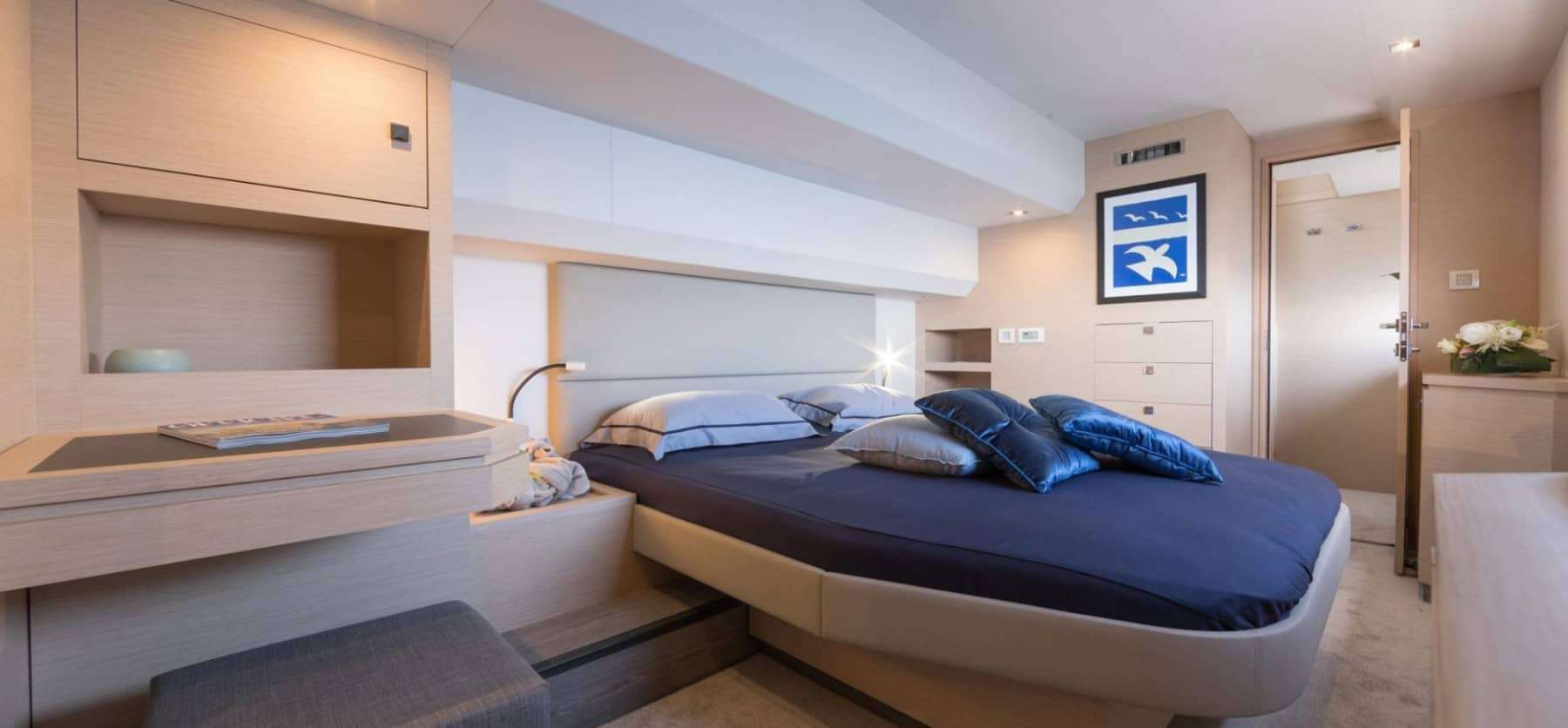 Spacious and elegant cabin of the Fountaine Pajot Motor Yacht 44 with a made bed with blue sheets