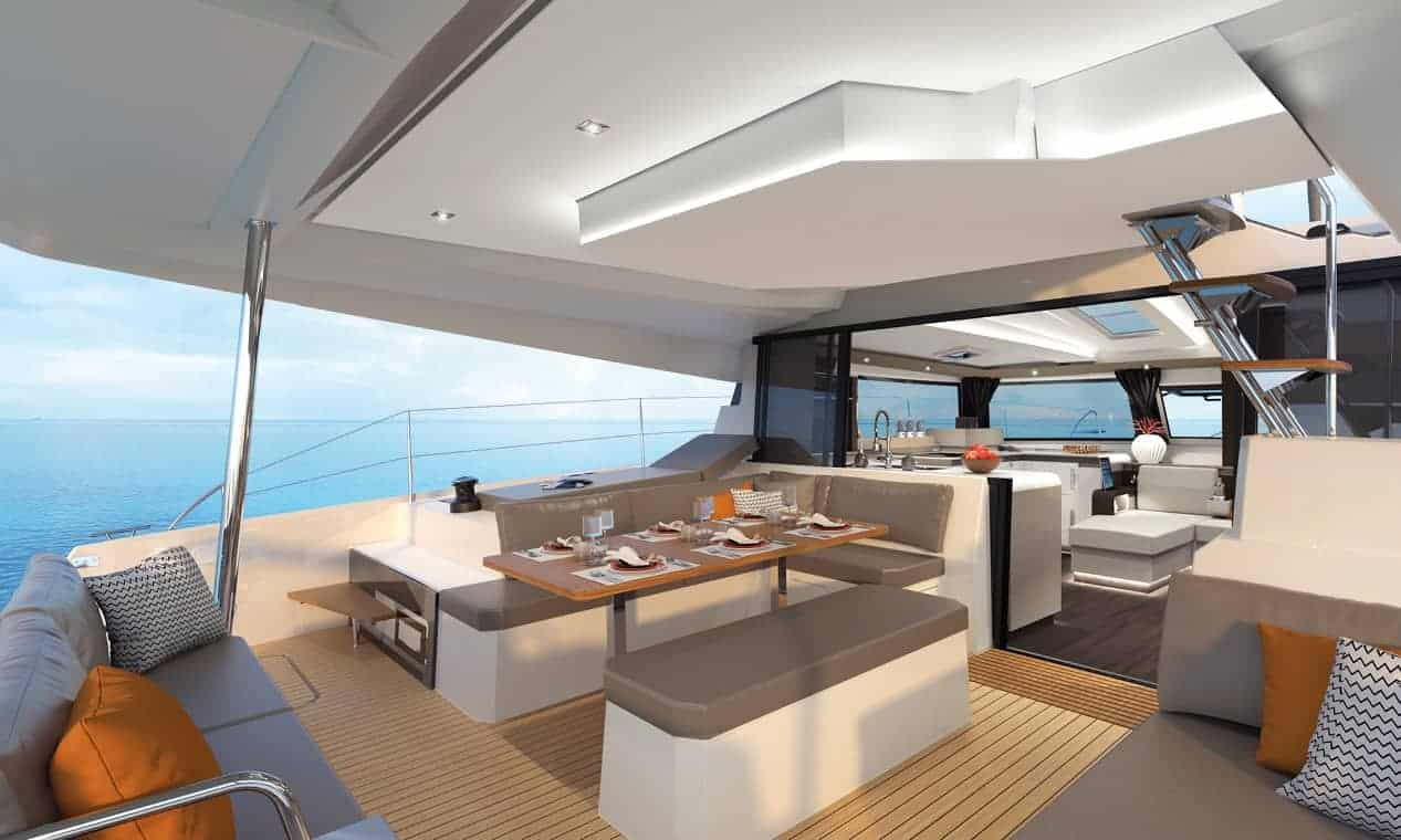 Deck of the modern and spacious Fountaine Pajot New 45 with set table and the amazing designed saloon and the horizon in the background