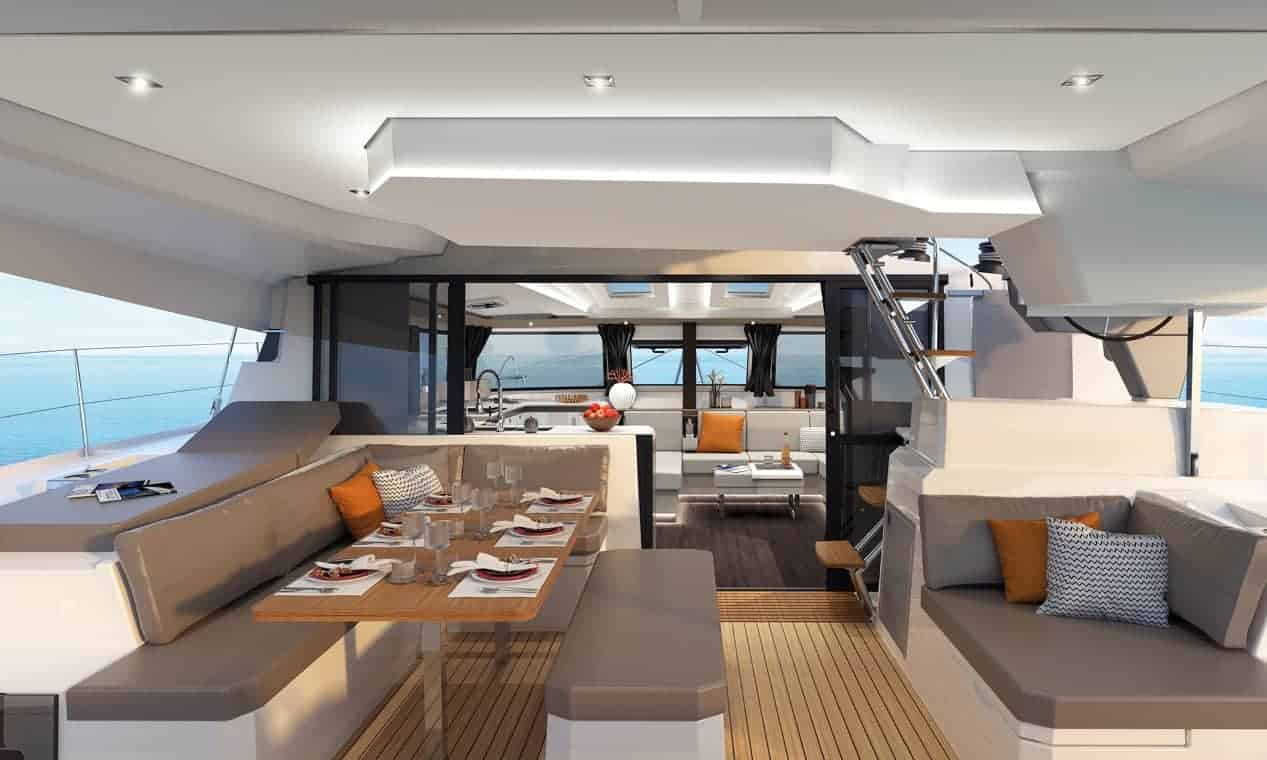 Deck of the modern and spacious Fountaine Pajot New 45 with set table and the amazing designed saloon in the background
