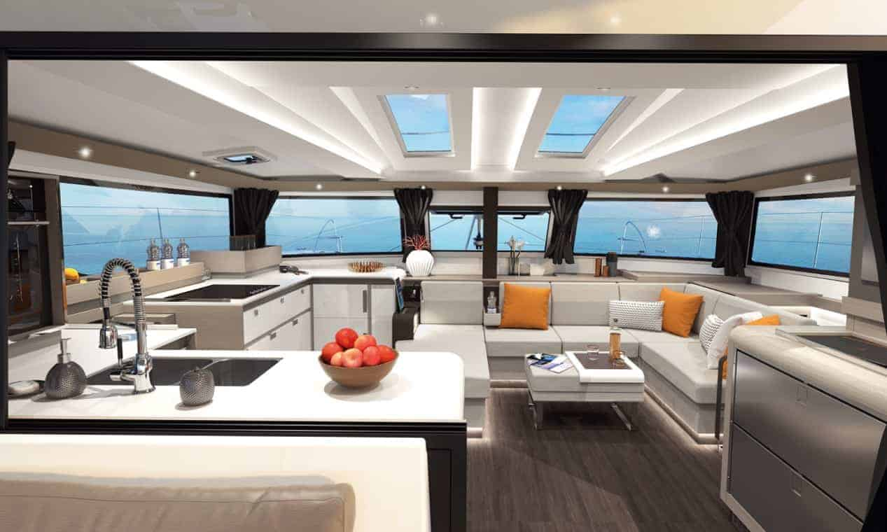 Overview of the stylish interior of the galley and saloon of the spacious Fountaine Pajot New 45 with modern design and orange pillows