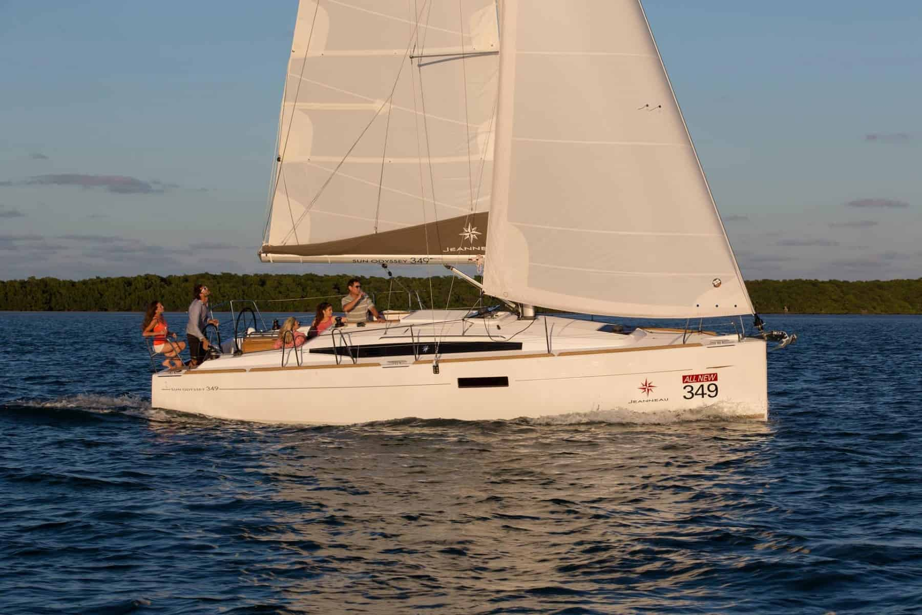 A Jeanneau Sun Odyssey 349 sailing on calm water with a party of people hanging out on deck