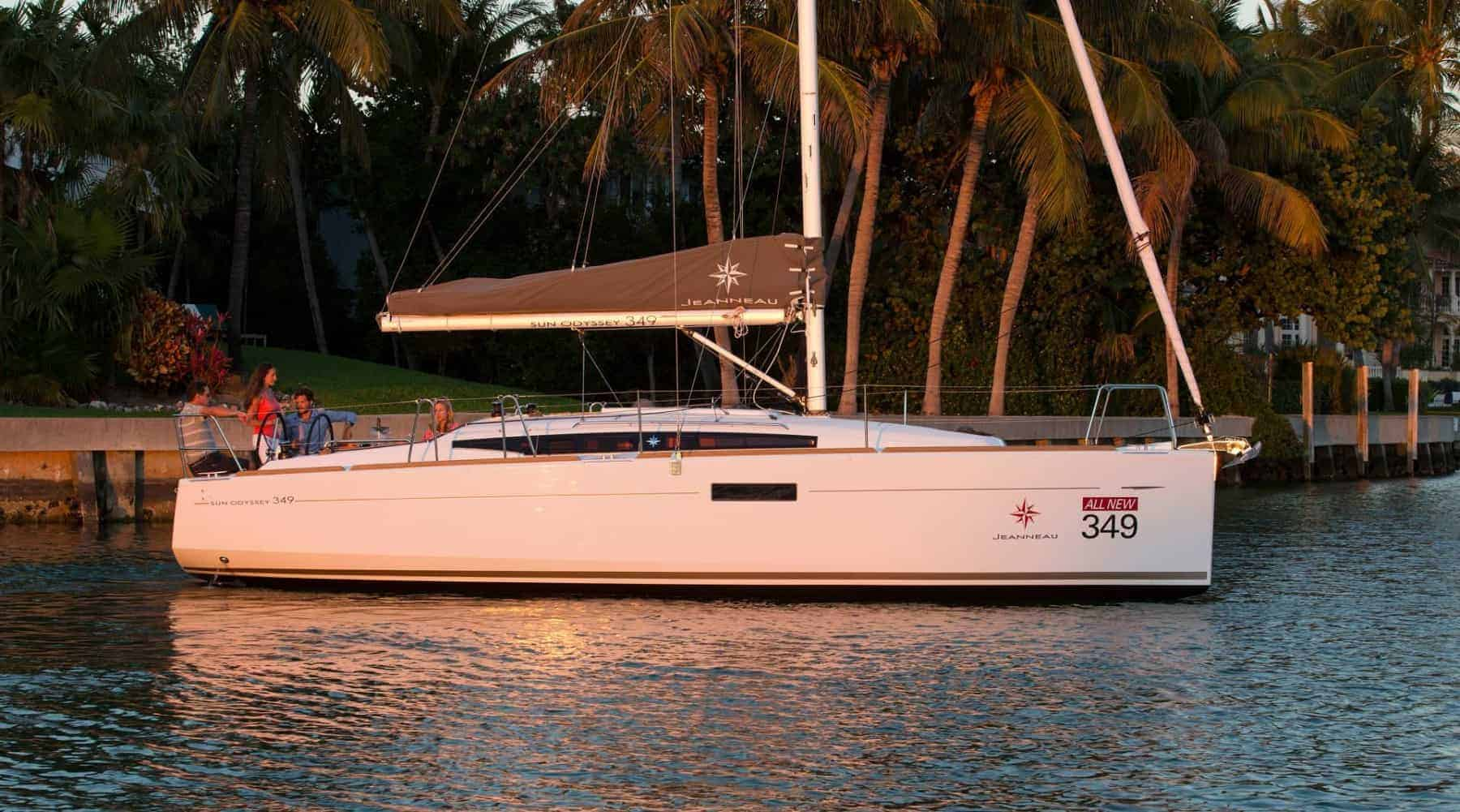 A docked Jeanneau Sun Odyssey 349 with the reflection of the sunset on it