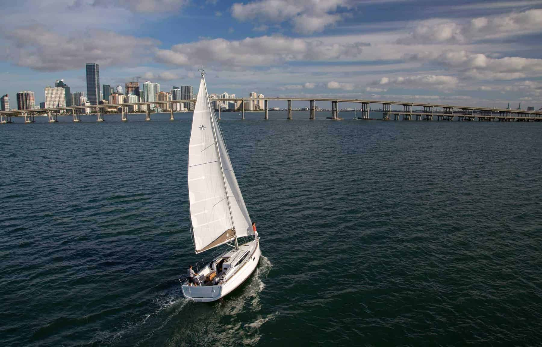 A Jeanneau Sun Odyssey 349 sailing towards a bridge close to a city during a sunny day