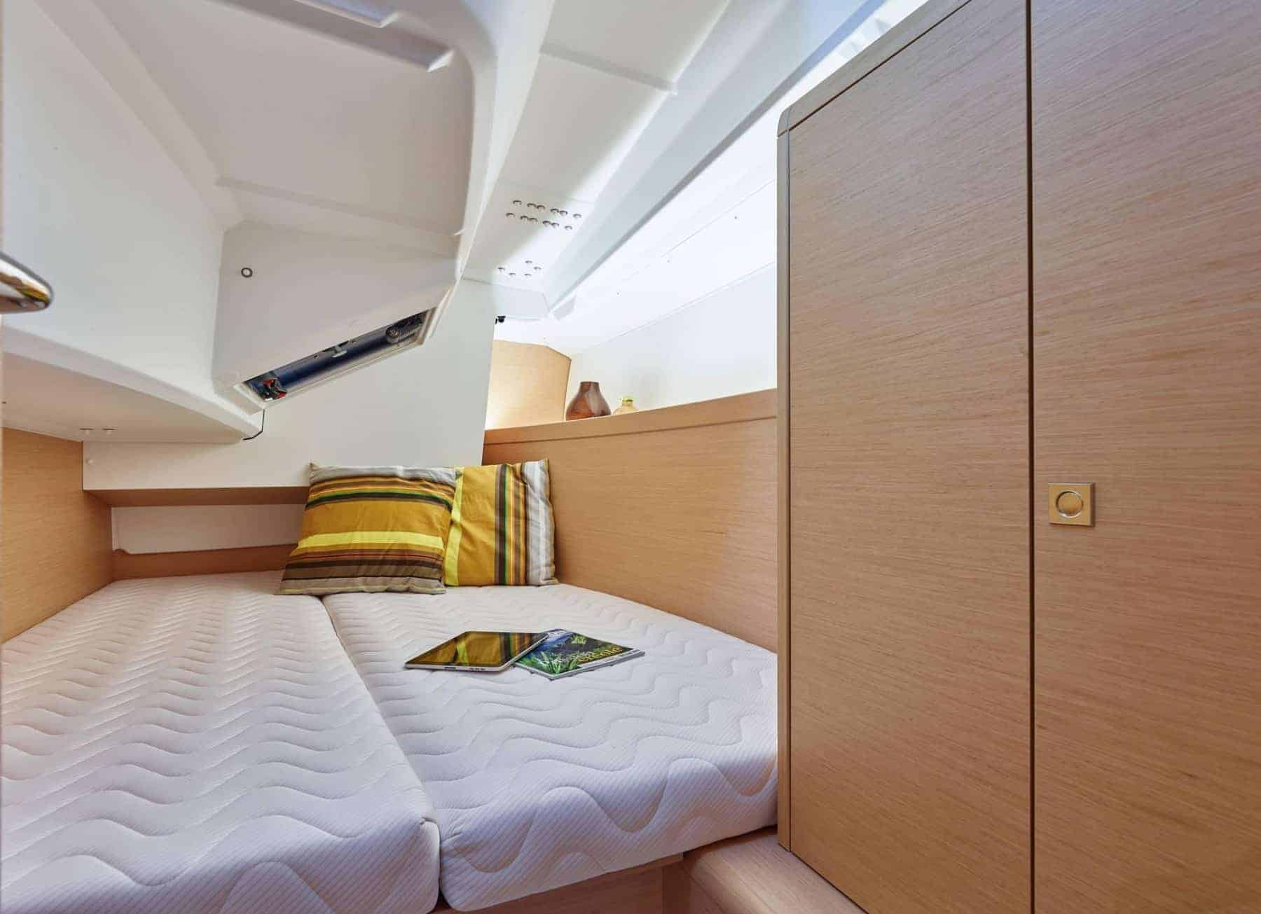 Bed in one of the cabins of the Jeanneau Sun Odyssey 349 with white ceiling and wooden panels