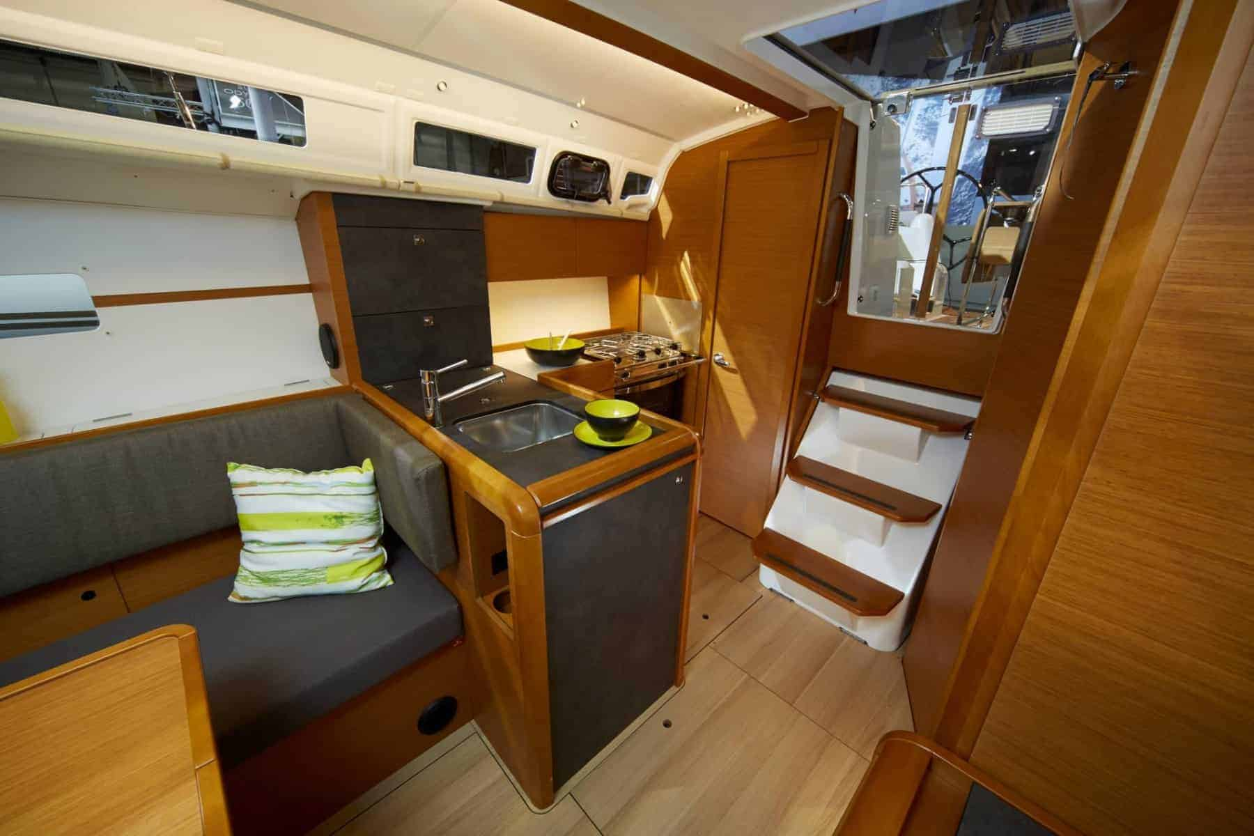 Inside of the saloon of the Jeanneau Sun Odyssey 349 showing the galley and the stairs leading up to deck