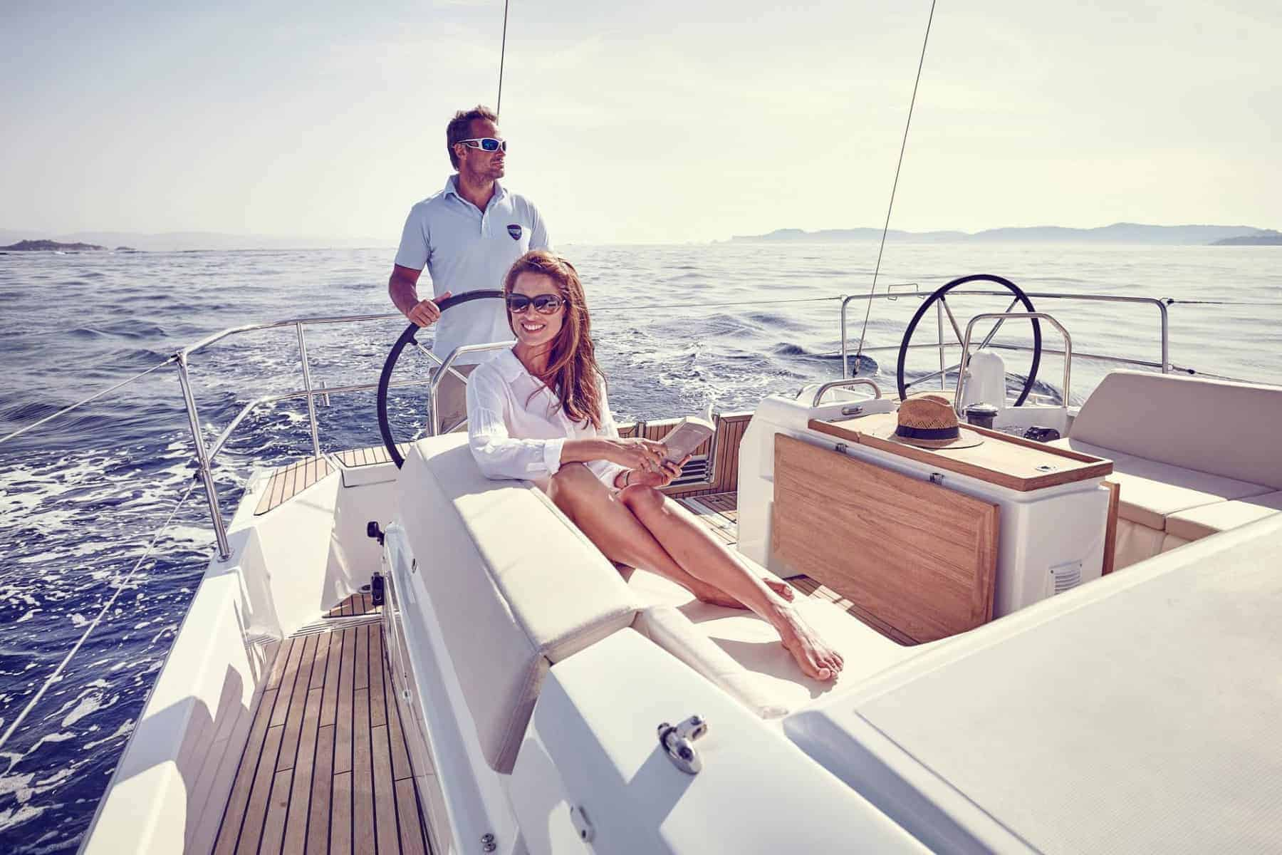 A couple hangs out in the cockpit of Jeanneau Sun Odyssey 440 with the man at the steering wheel