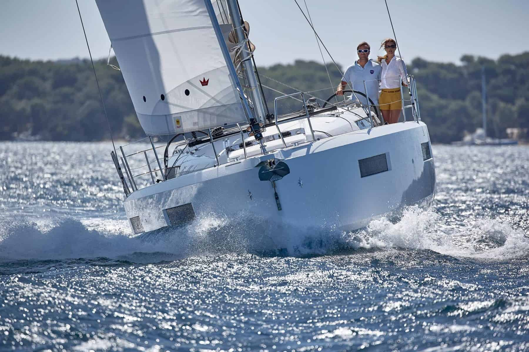 A Jeanneau Sun Odyssey 440 heading towards the camera with a man and a woman on deck