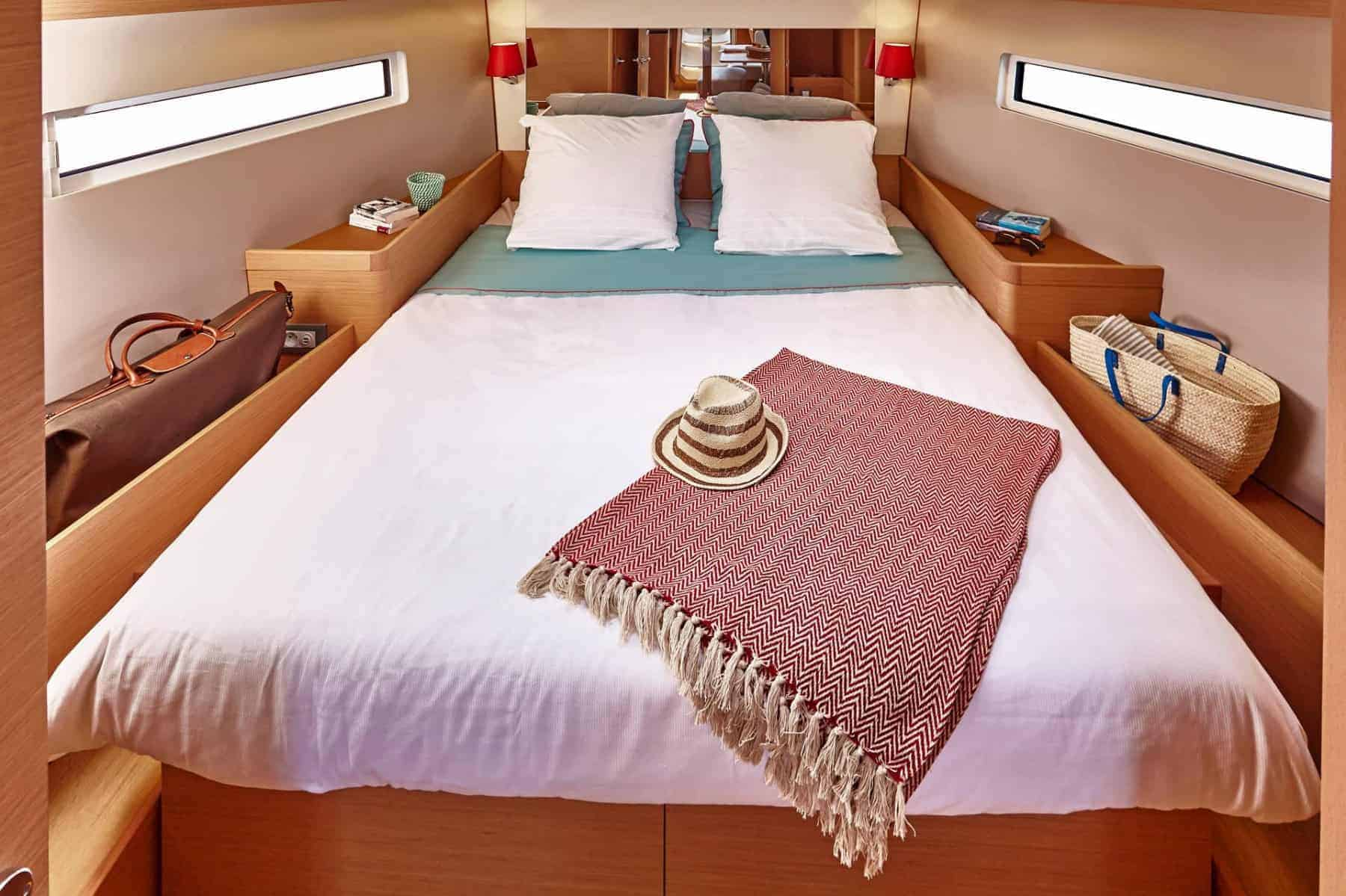 Made bed with a blanket and a hat on in a cabin of the gorgeous Jeanneau Sun Odyssey 440