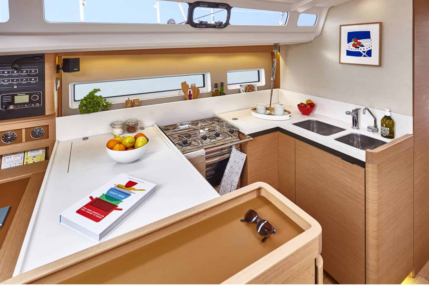 Galley of the Jeanneau Sun Odyssey 440 with a cookbook and bowl of fruit on the countertop