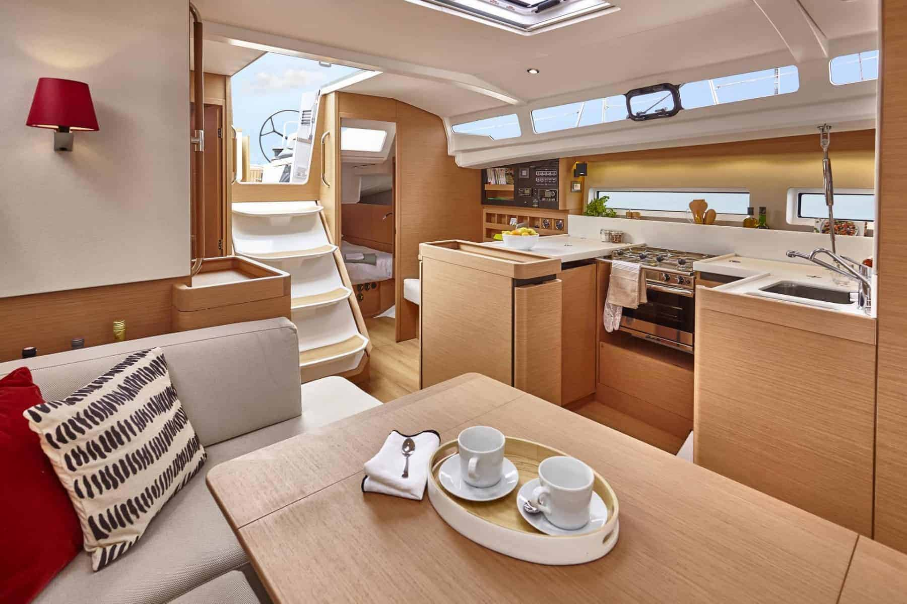 The light and beautiful saloon with white interior and red details of the Jeanneau Sun Odyssey 440