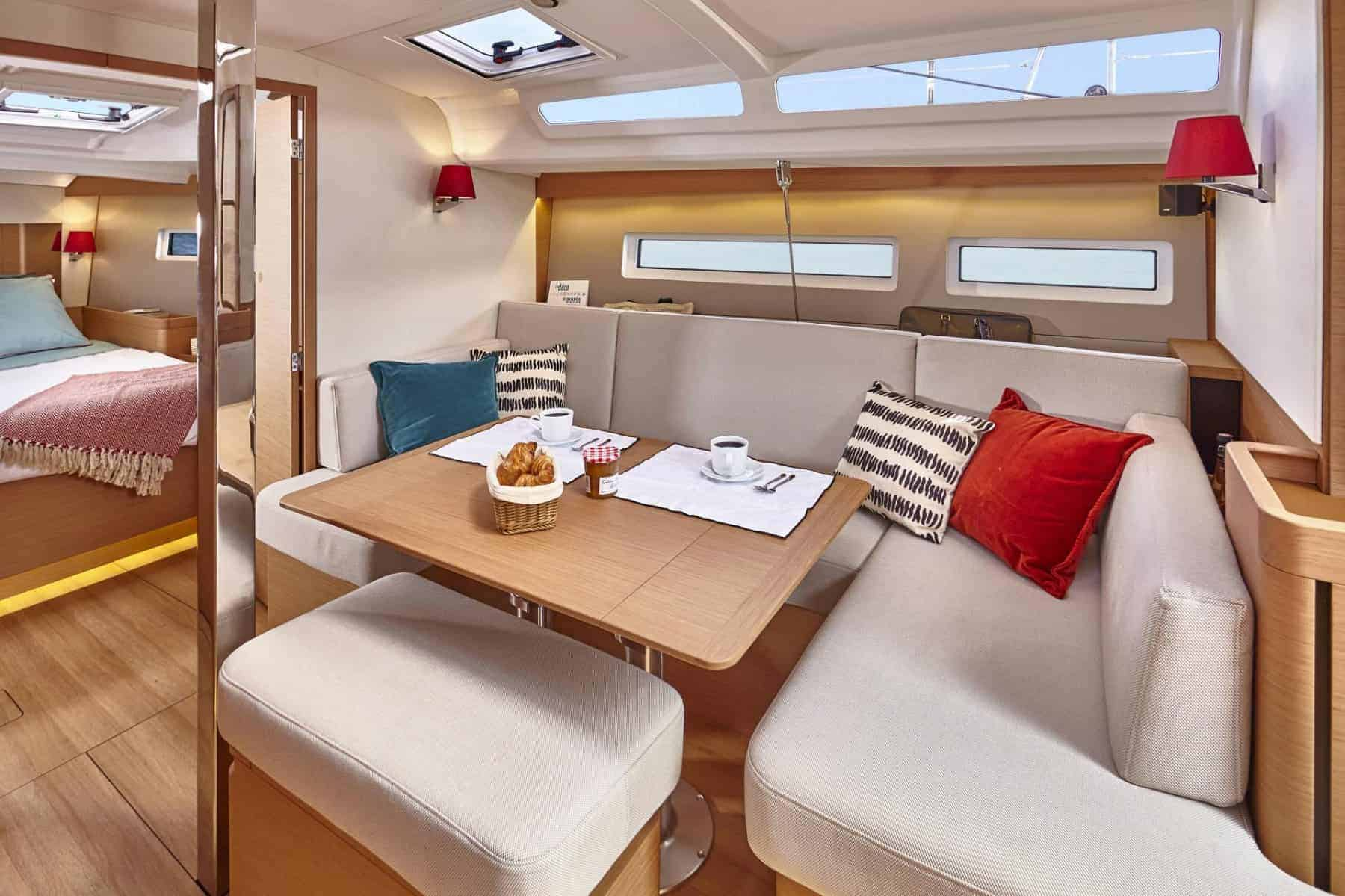 Folded out and set dinner table in the beautiful saloon of the Jeanneau Sun Odyssey 440