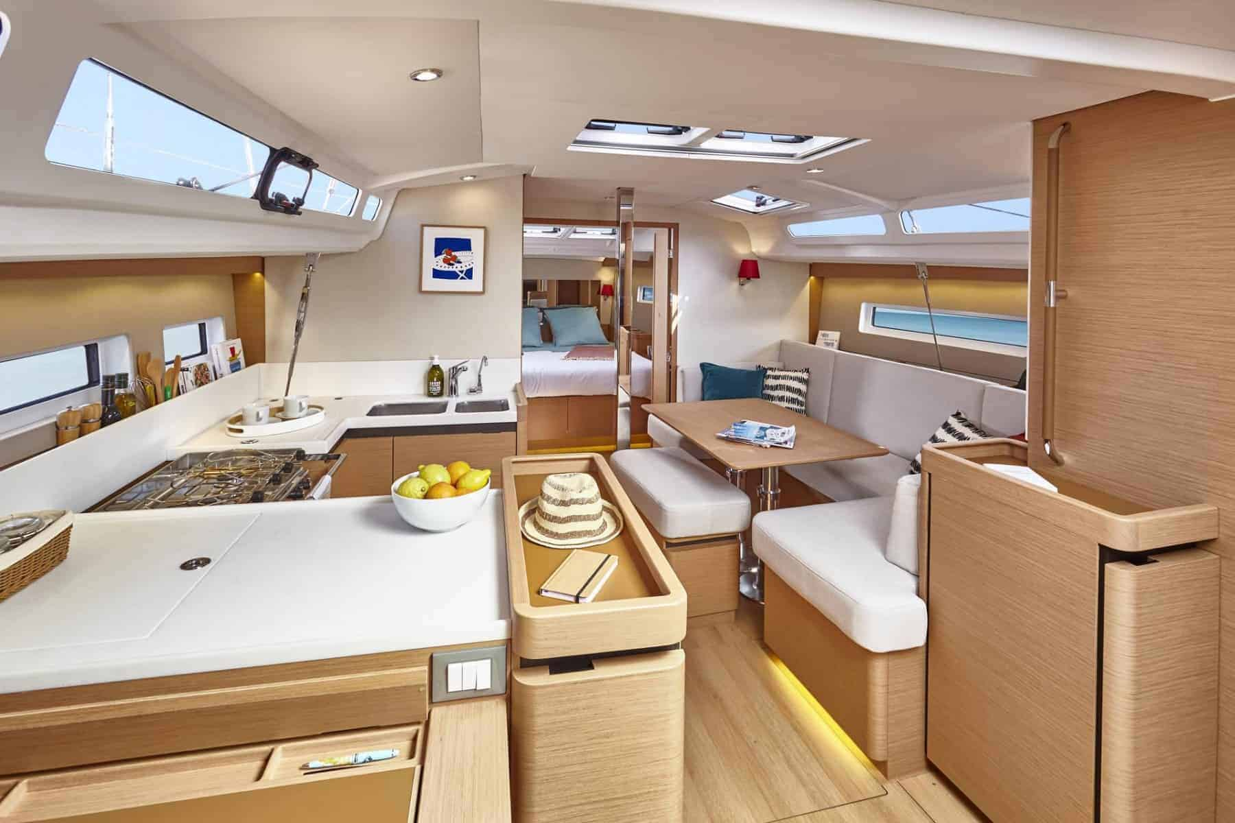 The open and spacious saloon of the elegant Jeanneau Sun Odyssey 440 with wooden interior