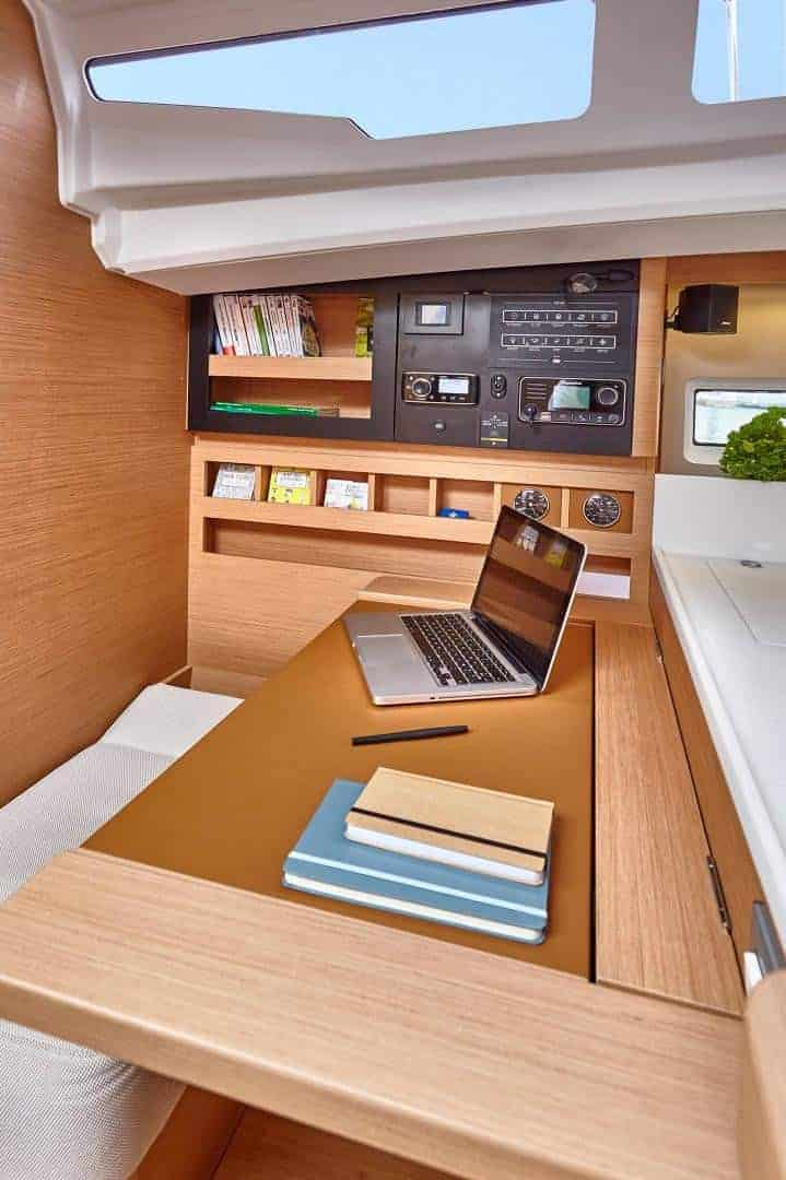 Crew cabin of the Jeanneau Sun Odyssey 440 with a bed, navigation board and a desk with a laptop on it